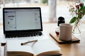 Foto de um computador, uma xícara e um livro com um lápis, como deve ser no NaNoWriMo - Photo by Nick Morrison